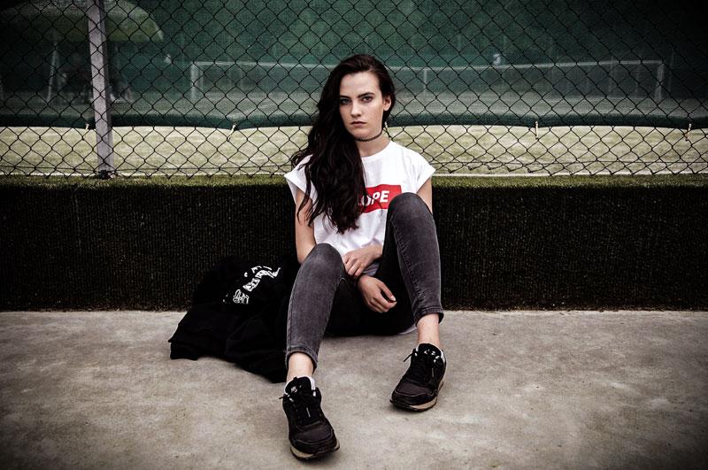 Mujer adolescente sentada en el suelo mirando a cámara