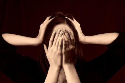 Mujer con manos en la cara y la cabeza
